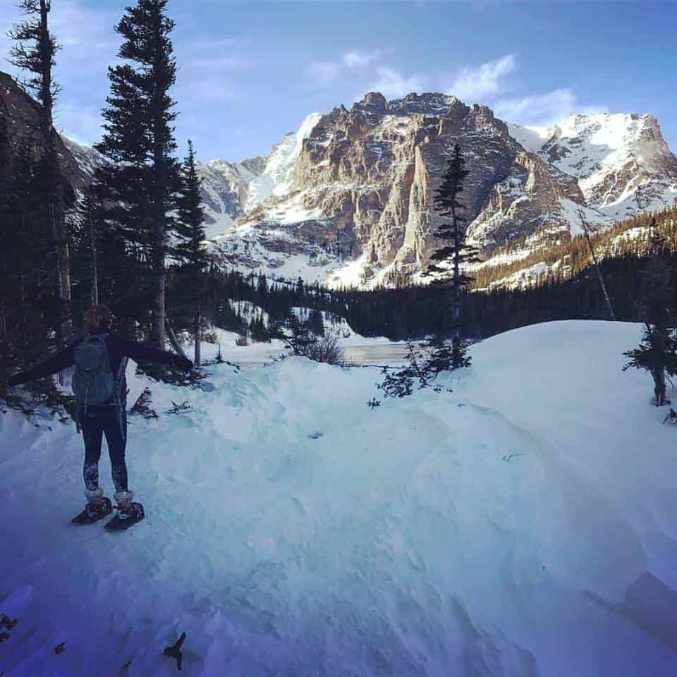 A woman takes in the view of the Lock with rugged mountains and blue skies in the background while snowshoeing in Rocky Mountain National Park