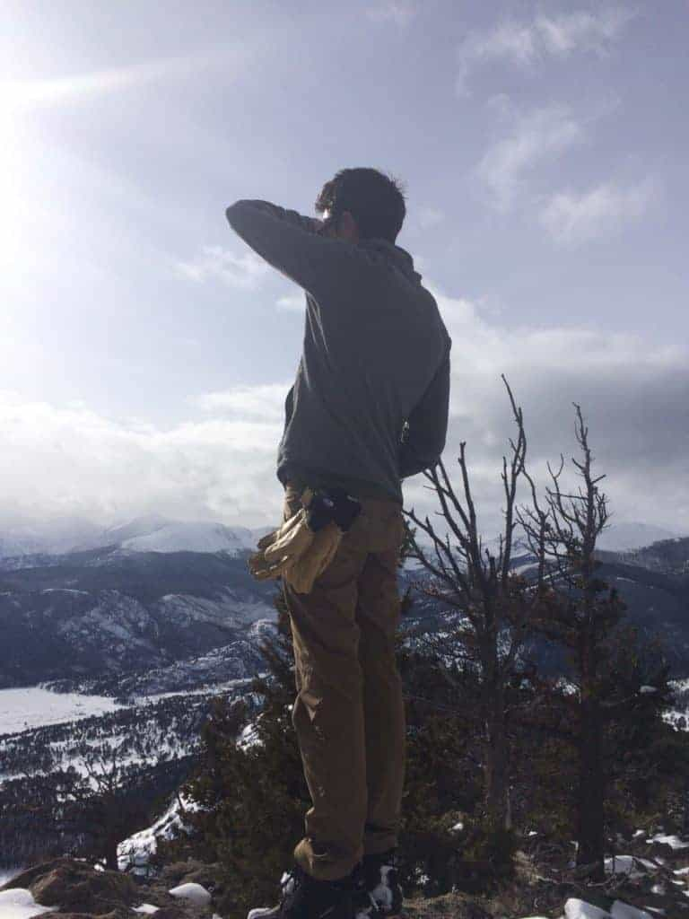 A man enjoys the views from the top of Deer Mountain while snowshowing in Rocky Mountain National Park