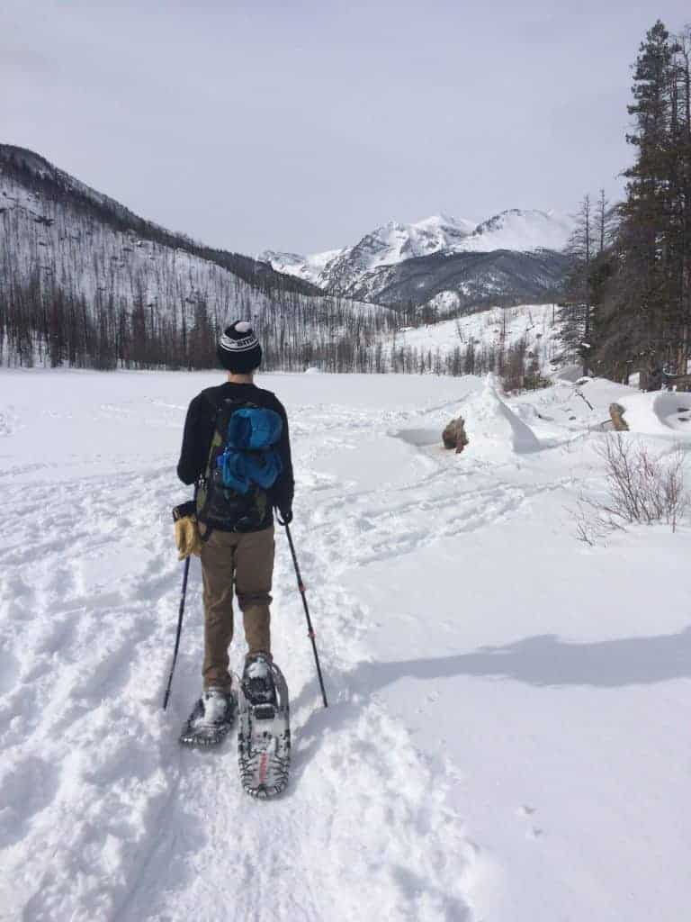 A snowshoer shown from behind with big mountains on the horizon in Rocky Mountain National Park.