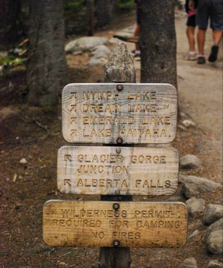 A wooden signboard showing trails to lakes in Rocky Mountain National Park.