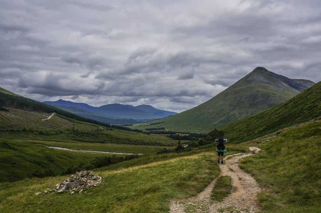A hiker walks along the West Highland Way with views of Beinn Dorain in the distance.