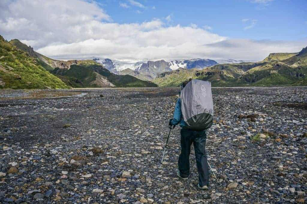 A hiker walks on rocky terrain on the Laugavegur Trail