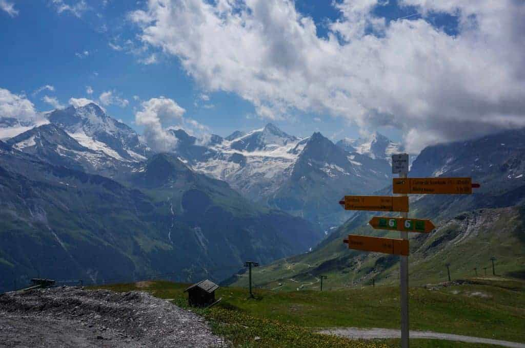 Trail sign with mountains in the background on the Walker's Haute Route.