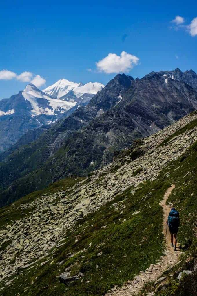 A trekker seen from behind heads towards snow capped mountains on the Walker's Haute Route