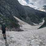 A hiker crosses a large snow field on stage 9 of the Walker's Haute Route