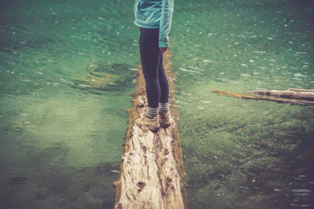 A woman stands on a log that juts into turquoise water. Footwear on the Walker's Haute Route.