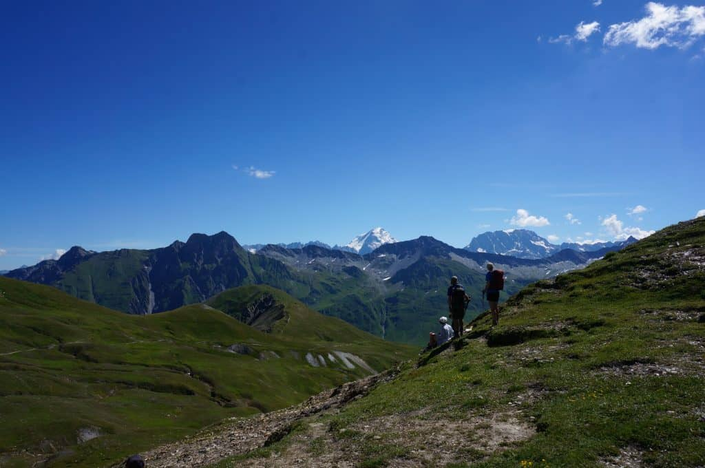 Hikers take in the views from the top of a pass on the TMB