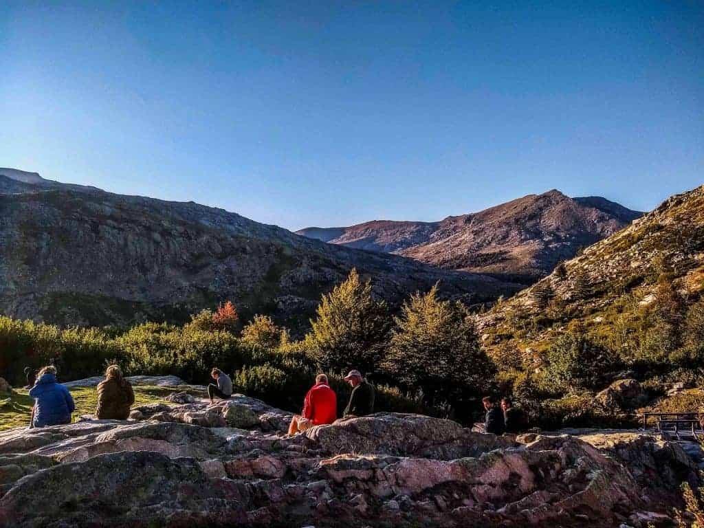 Trekkers sitting on rocks at Refuge de Manganu.