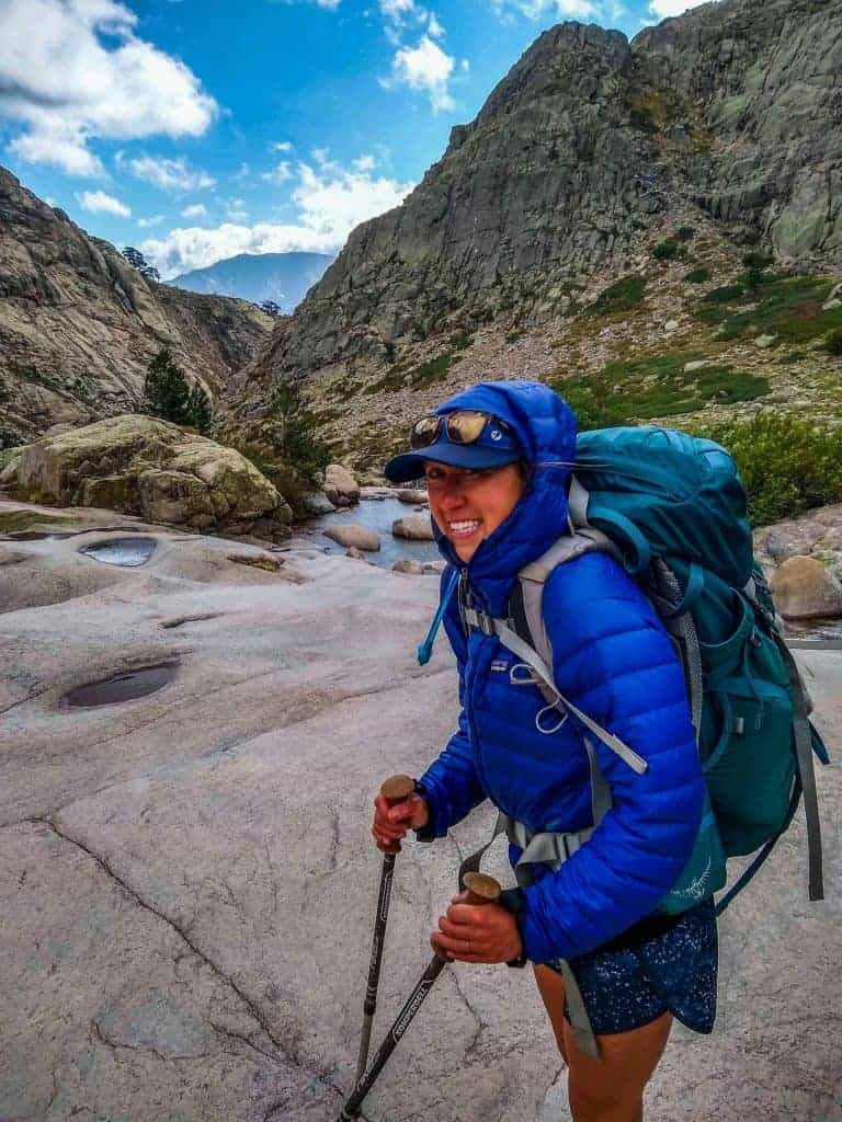 Hiker with a backpack and trekking poles on the GR20