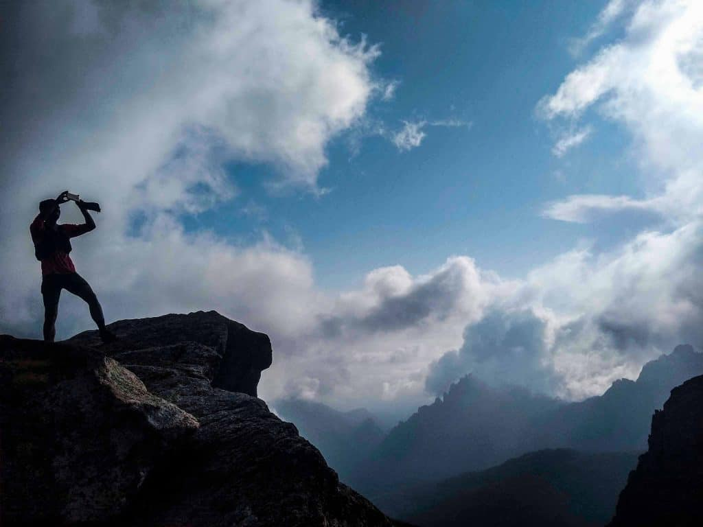 Hiker silhouetted against clouds on the GR20.