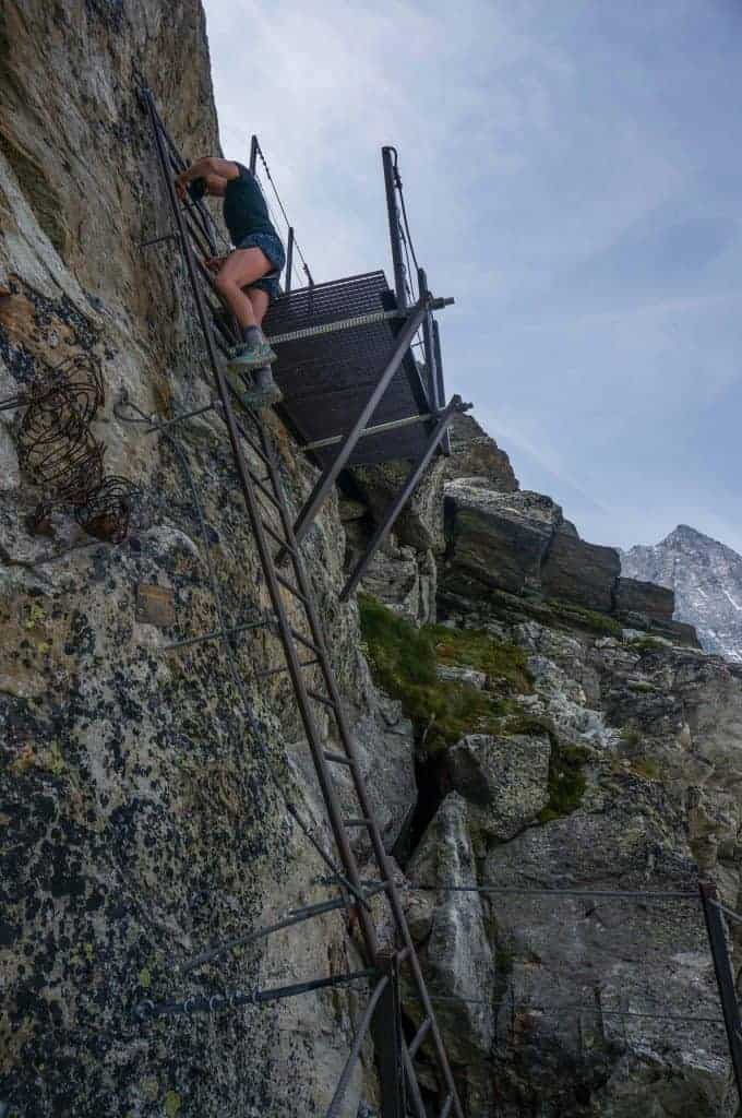 Hiker climbs a ladder to reach Pas des Chevres on the Walker's Haute Route