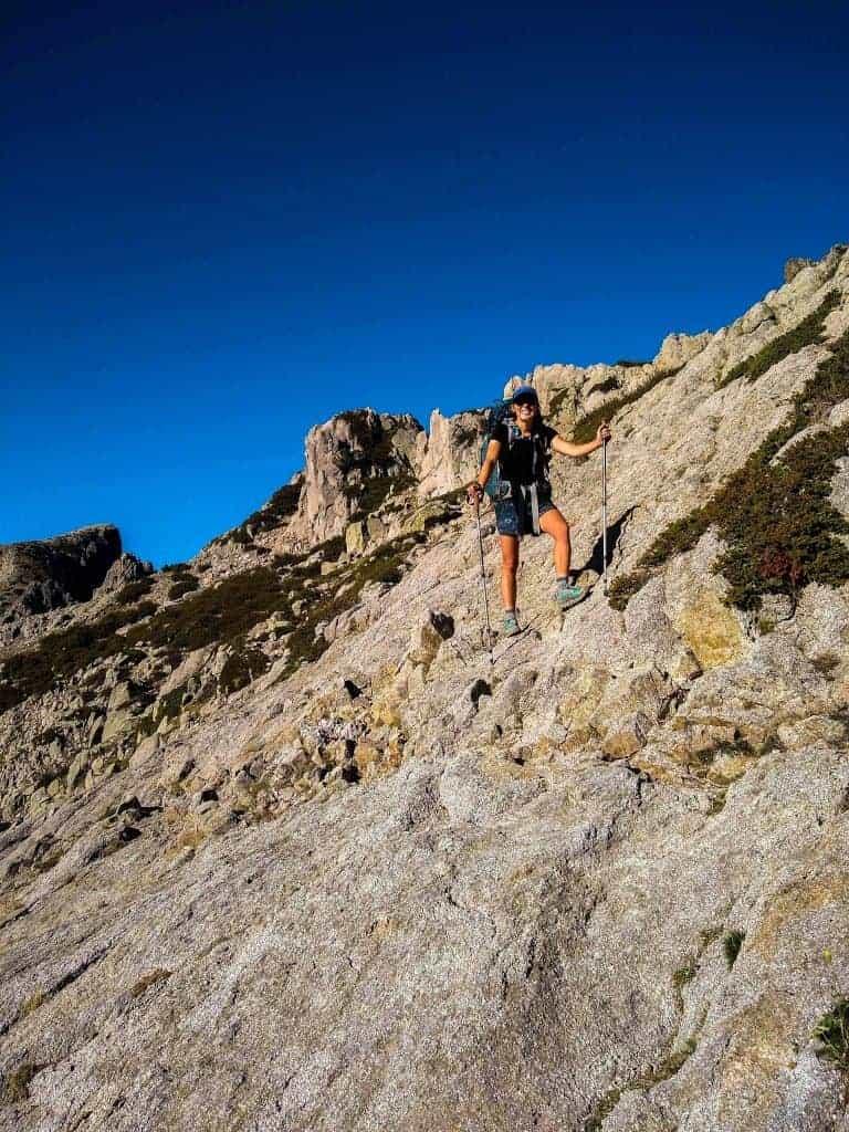 Hiker crosses a large rock slab on Stage 14 of the GR20