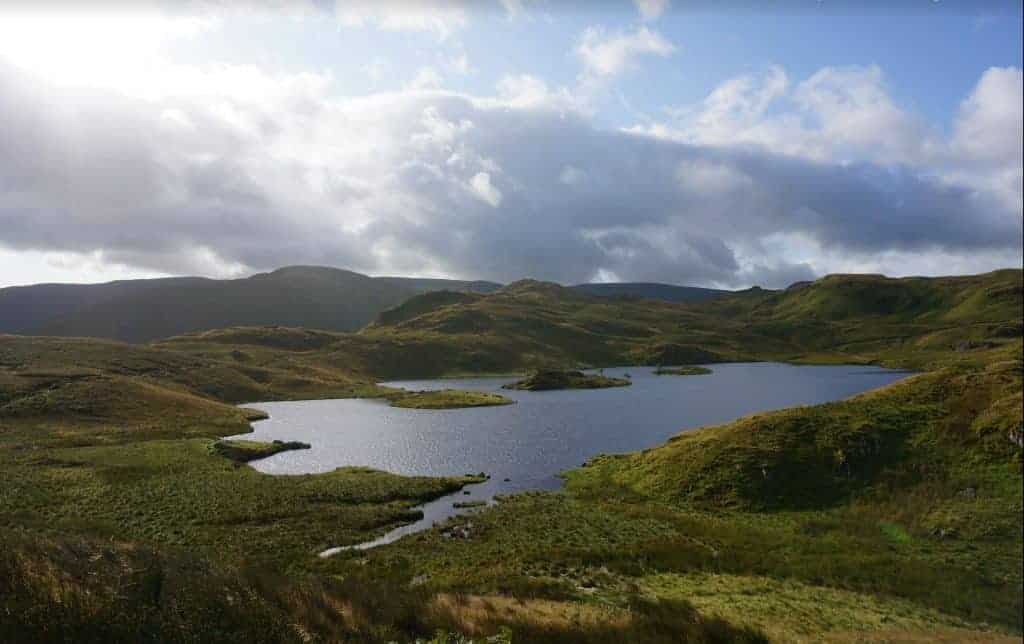 Looking out over a tarn and green hills in England's Lakes District on the Coast to Coast Walk