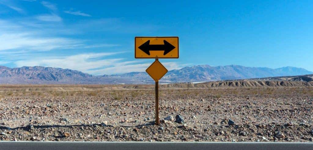 Road sign with mountains in the background