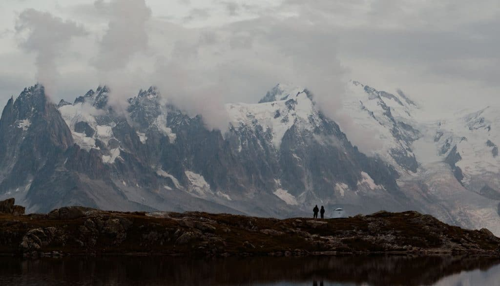 Hikers stand next to Lac Blanc on the TMB