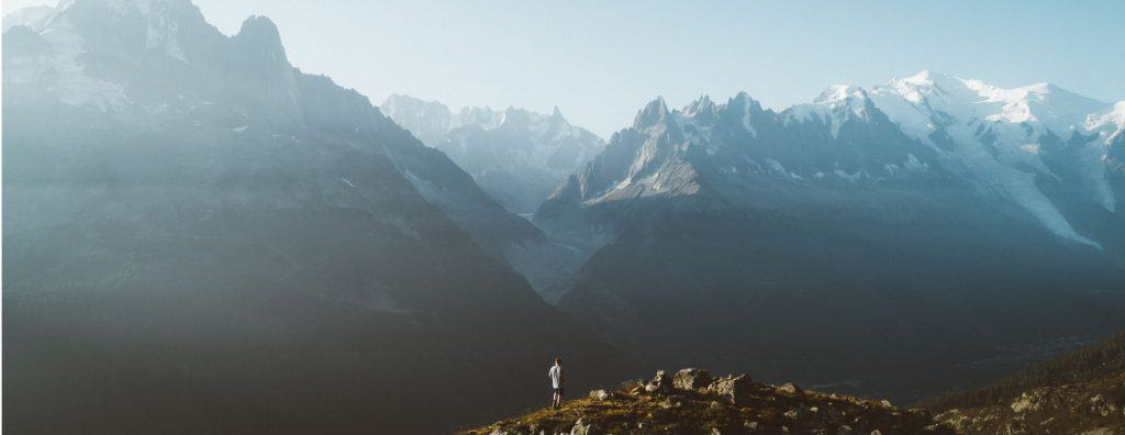 A hiker looks out over Mont Blanc