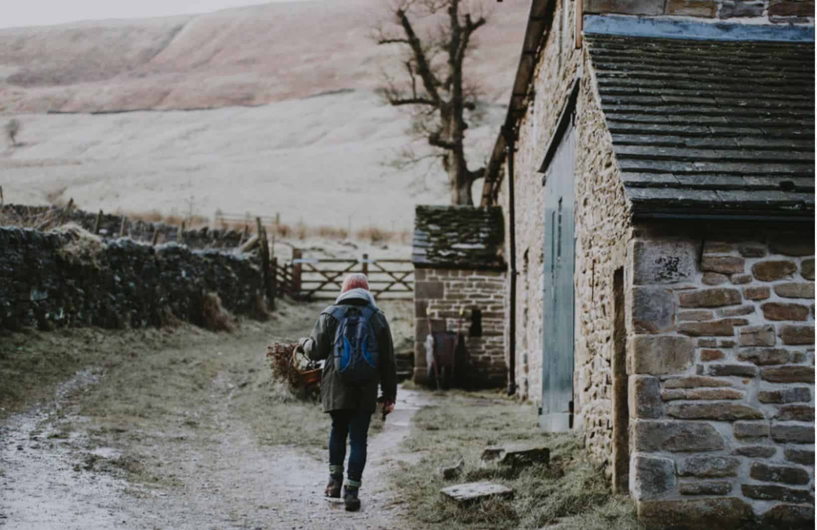Person outside a stone cottage