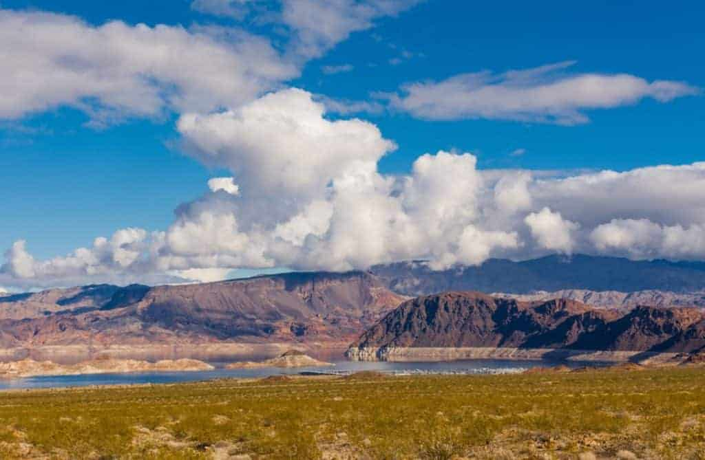 Lake Mead with bluffs in the background under a blue sky.