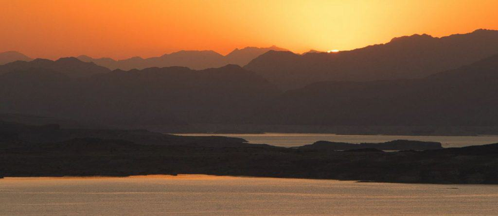 Sunset over Lake Mead with mountains in the background.