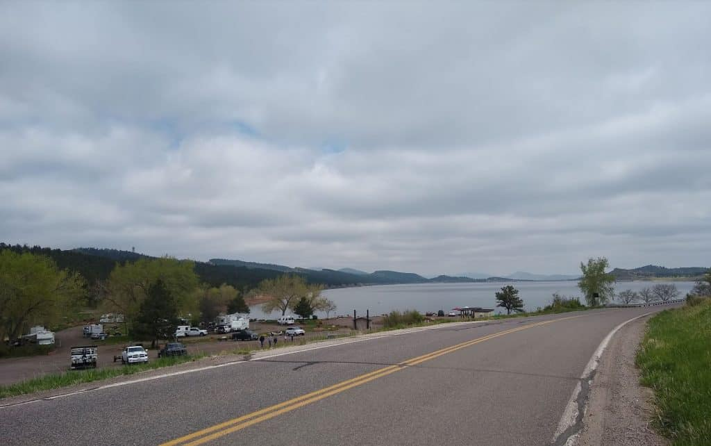 A paved road with Carter lake in the background