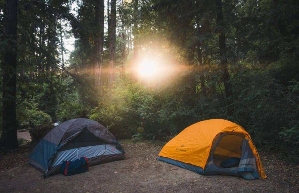 A blue and an orange tent with sunlight coming through the trees.