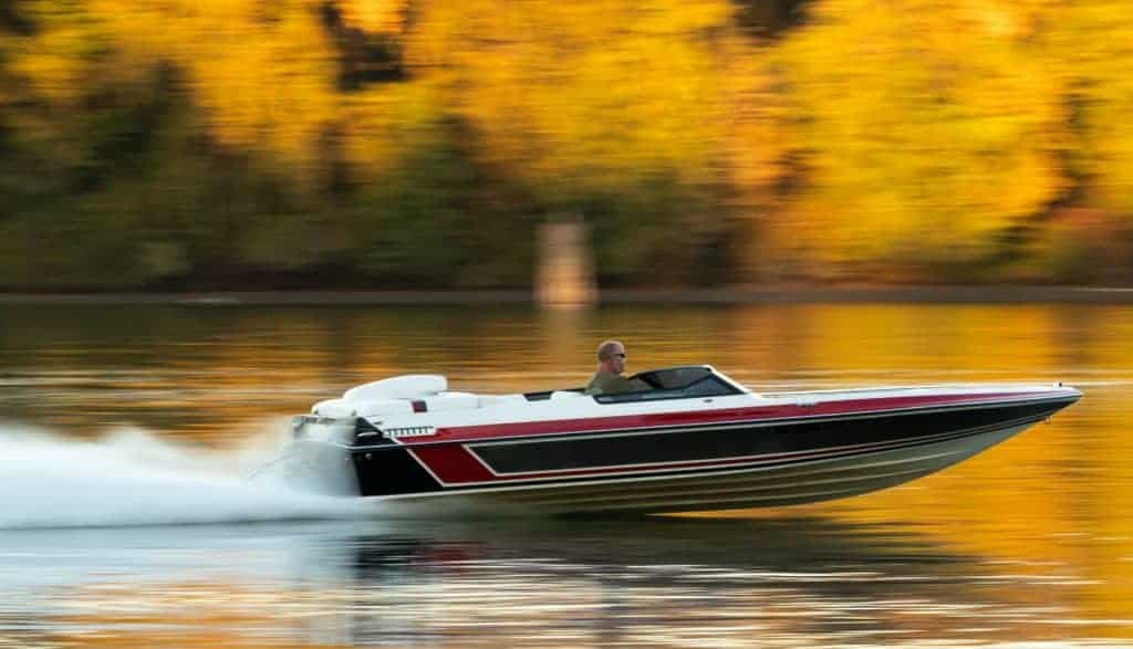 A speedboat with autumn trees in the background